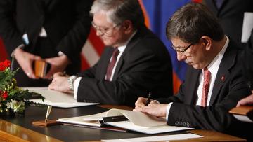 Эдуард Налбандян и Ахмет Давутоглу подписывают документы во время церемонии заключения мирового соглашения между Арменией и Турцией