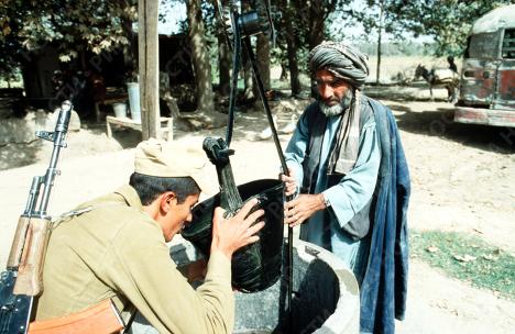 Находящийся в Афганистане советский солдат пьет воду из ведра местного жителя.