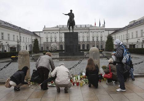 Люди приносят цветы к президентскому дворцу в Варшаве