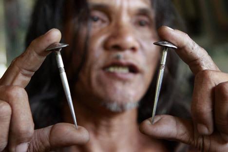 Кающийся Рубен Эньяж показывает две трехдюймовых стальных гвоздя, сделанных на заказ, которые будет использоваться для его распятие в Страстную пятницу в Катуд, Сан-Фернандо Пампанга в северной части Филиппин