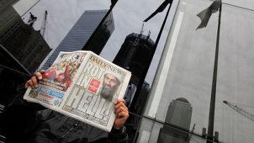 Мужчина читает газету с заголовком о ликвидации Усамы бен Ладена в центре Нью-Йорка