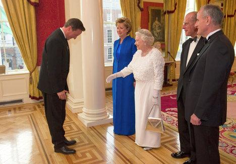 королева Великобритании Елизавета II, принц Филипп, президент республики Ирландия Мэри Макэлис и ее супруг Мартин Макэлис встречают премьер-министра Великобритании Дэвида Кэмерона в Дублинском замке