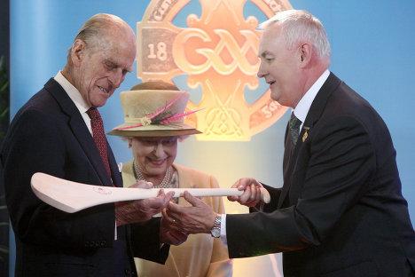 королева Великобритании Елизавета II и герцог Эдинбургский Филип на стадионе Кроук-парк получают в подарок клюшку и мяч для игры в херлинг