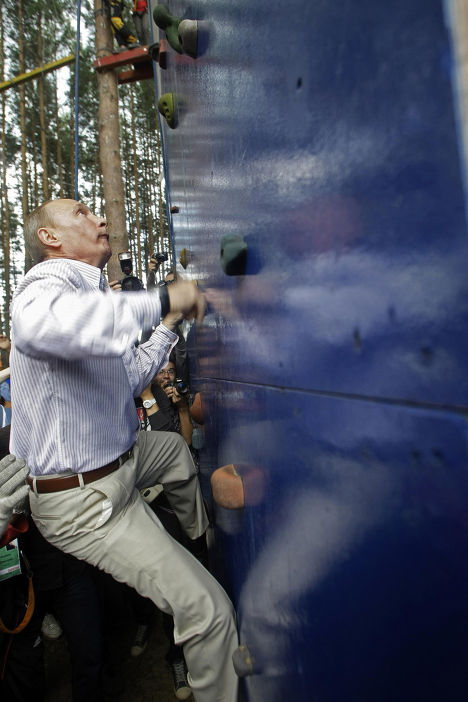 Премьер-министр России Владимир Путин взбирается на стену для скалолазания в ходе визита на Селигер