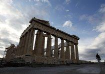 Турист проходит мимо здания Акрополя в Афинах