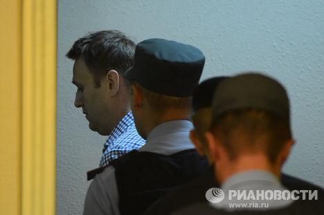 Сотрудники полиции уводят из зала суда Алексея Навального