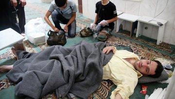 Люди помогают пострадавшим от газовой атаки в мечети в окрестностях Дамаска