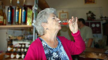 Пожилая женщина пьет алкогольный напиток