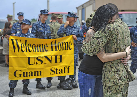 Моряк, вернувшийся из четырехмесячного плавания по Юго-Восточной Азии, обнимает жену на острове Гуам