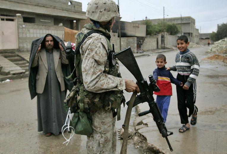 Американский солдат патрулирует улицу в Эль-Фаллудже в Ираке