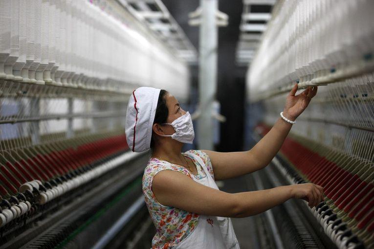 Женщина работает на текстильной фабрике в Китае
