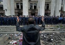 Человек обращается к милиции, охраняющей сожженное здание Дома профсоюзов в Одессе
