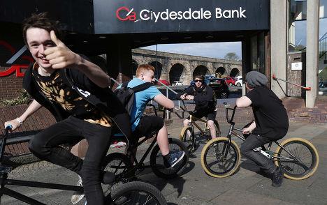 Школьники катаются на велосипедах после занятий в городе Килмарнок в Шотландии