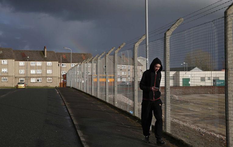 Человек проходит мимо места, где раньше находился завод Johnnie Walker