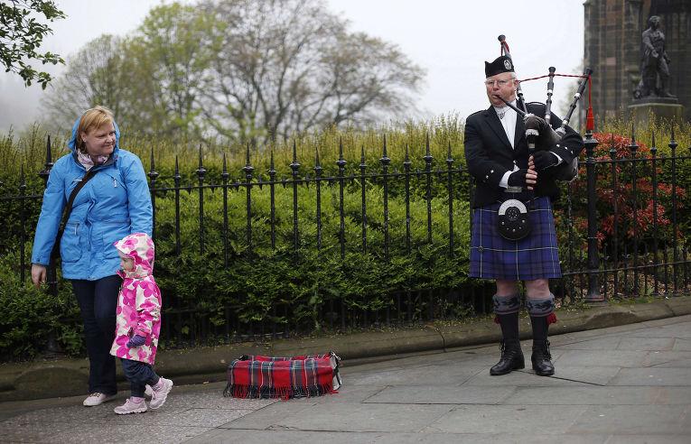Музыкант играет на волынке на улице в Эдинбурге