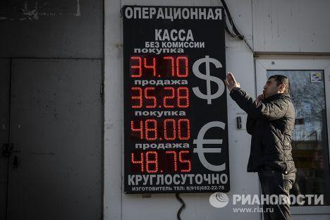 Мужчина у пункта обмена валюты в Москве