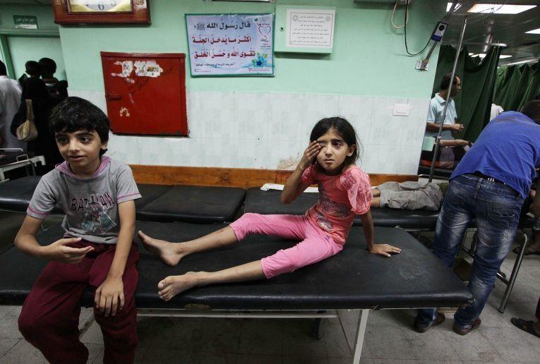 Палестинские дети, пострадавшие во время бомбардировки школы ООН в секторе Газа