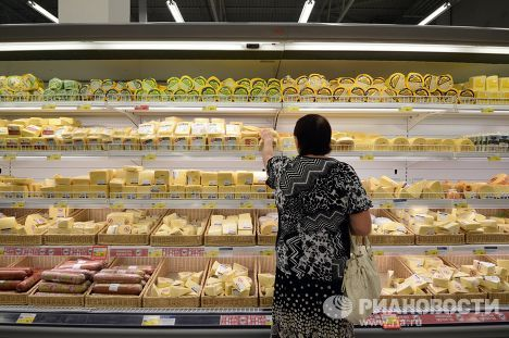 Женщина у прилавка с сырами в гипермаркете
