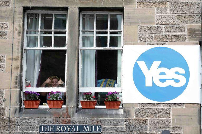 Женщина разместила возле окна плакат в поддержку независимости Шотландии в Эдинбурге