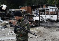 Ополченец рядом с автомобилями, поврежденными во время артобстрела Донецка
