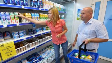 Покупатели у полки с молочной продукцией