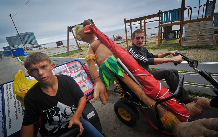 Сотрудники фирмы по развлечению туристов вывозят аксессуары со склада на набережную города Владивостока