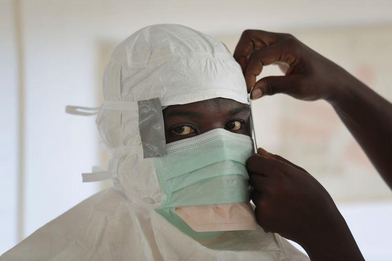 Медсестра из организации «Врачи без границ» готовится к входу в зону высокого риска в Центре по лечению Эболы в Монровии
