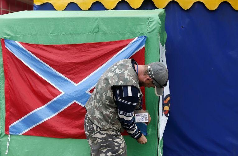 Ополченец вешает флаг Новороссии в Донецке