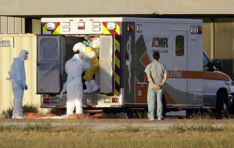 Медицинские работники сопровождают Нину Фам, больную лихорадкой Эбола