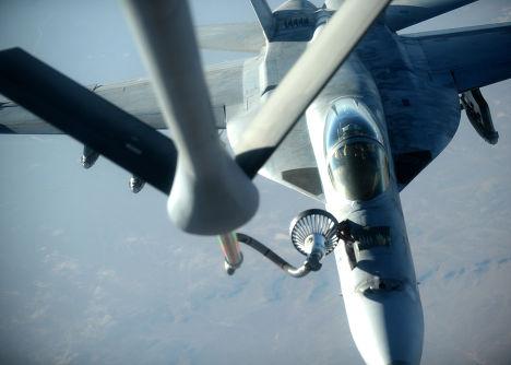 Истребитель F-18E Super Hornet заправляется от самолета-заправщика KC-135 Stratotanker после нанесения авиаудара по силам Исламского государства