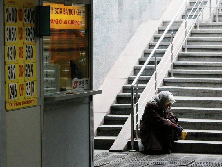 Женщина сидит рядом с пунктом обмена валют в Киеве, Украина. 26 февраля 2014