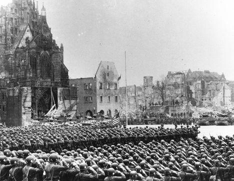 Американцы устанавливают флаг на площади Адольфа Гитлера в Нюрнберге, 20 апреля 1945 года