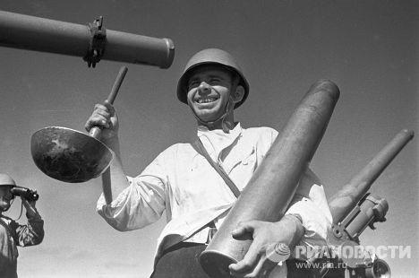"""Кок эсминца """"Фрунзе"""" Г. Пронин стоит с половником в одной руке и гильзой от снаряда в другой. Оборона Одессы"""