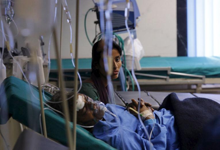 Женщина сидит рядом с родтсвенником, раненным во время землетрясения в Катманду, Непал