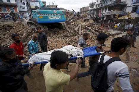 Спасатели несут тело жертвы землетрясения в Катманду