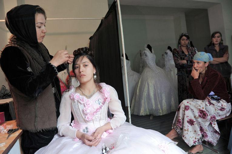 Парикмахер делает невесте прическу в свадебном салоне города Душанбе в Таджикистане