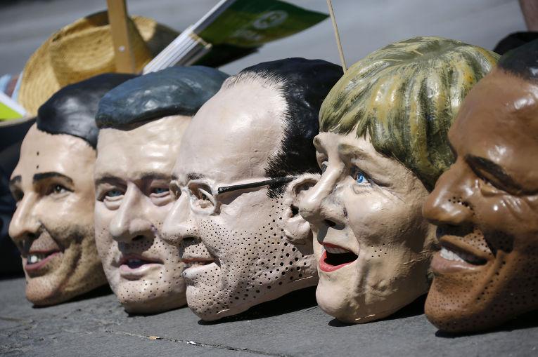 Маски с лицами участников саммита G7 во время акции протеста в Мюнхене