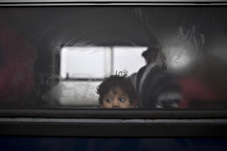 Ребенок из Сирии в автобусе, который отвезет его семью в лагерь для беженцев неподалеку от города Рёске, южная Венгрия
