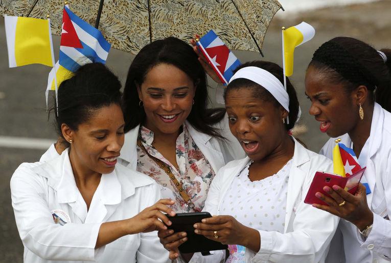 Медсестры с флагами Кубы и Ватикана в волосах ждут проезда папамобиля