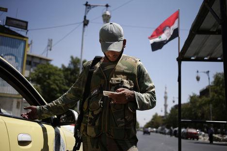 Сирийский военный проверяет документы на блокпосту в Дамаске
