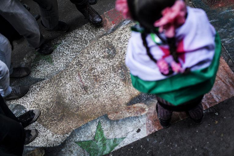 Растоптанный портрет Башара Асада во время протестов в Алеппо, 2013 год