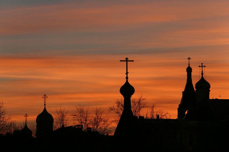 Силуэты церквей в центре Москвы на фоне закатного неба