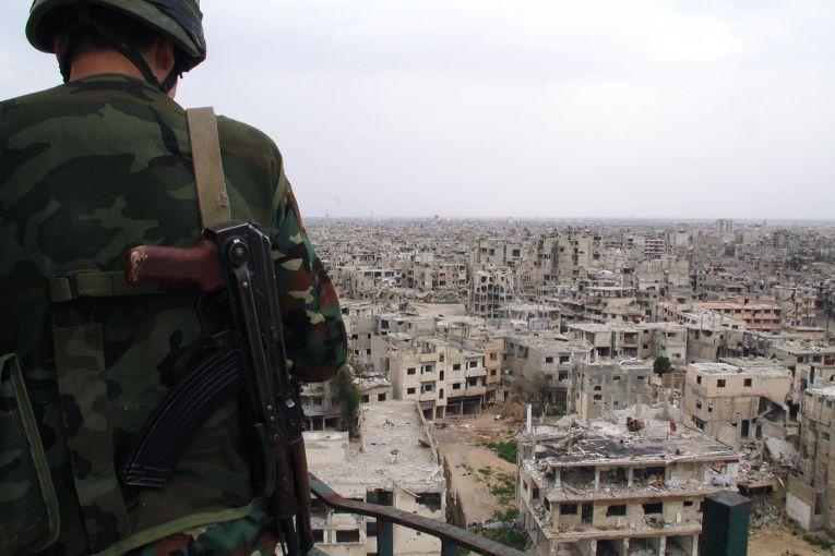 Военнослужащий сирийской армии на крыше одного из зданий, разрушенных в результате боевых действий, в Хомсе