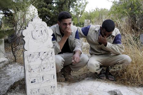Работники группы сирийской гражданской обороны у могилы своего сослуживца, погибшего, по их словам, во время российского авиаудара