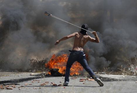Демонстрант из Палестины бросает камни в сторону войск Израиля в ходе столкновений в Иерусалиме. Октябрь 2015