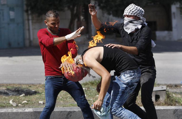 Палестинцы помогают соотечественнику сбить пламя, перекинувшееся на него из бутылки с зажигательной смесью, которую он пытался бросить в израильских полицейских