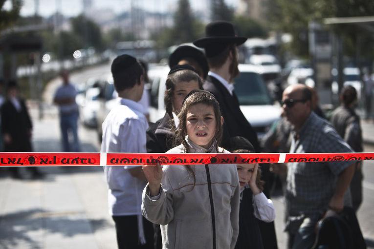Мальчик из семьи ортодоксальных евреев смотрит на место нападения палестинца на студента семинарии в Иерусалиме
