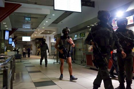 Израильские полицейские обыскивают центральную автобусную станцию Иерусалима, где было совершено нападение на женщину
