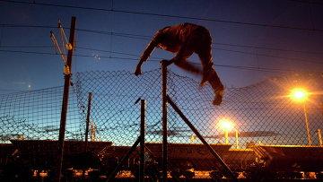 Мигрант пытается пробраться в Евротоннель в Кале, Франция