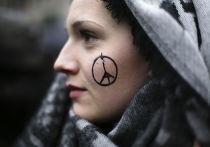 Символ «Мир Парижу» на лице у девушки во время минуты молчания у французского посольства в Берлине